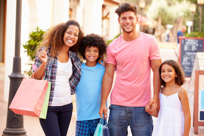 Retrato de la familia que camina a lo largo de la calle con los panieres imagen de archivo libre de regalías