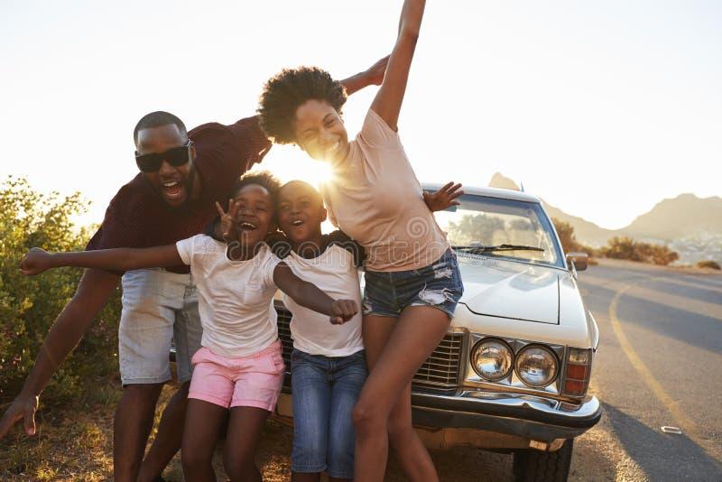 Retrato de la familia que se coloca al lado del coche clásico imagen de archivo