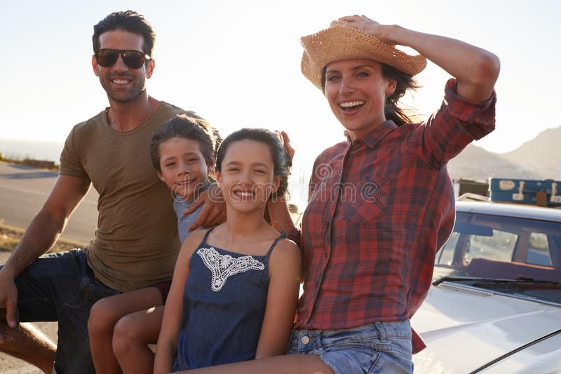 Retrato de la familia que se coloca al lado del coche clásico imagenes de archivo