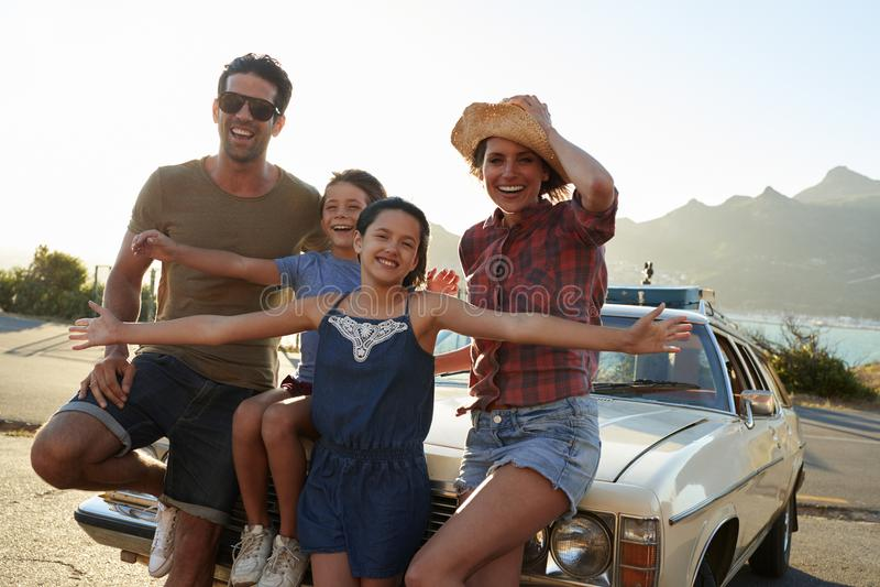 Retrato de la familia que se coloca al lado del coche clásico fotos de archivo