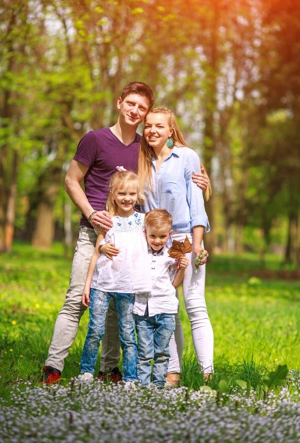 Retrato de la familia que se divierte en parque de florecimiento de la ciudad en el día soleado brillante que pasa feliz su tiemp imagen de archivo libre de regalías