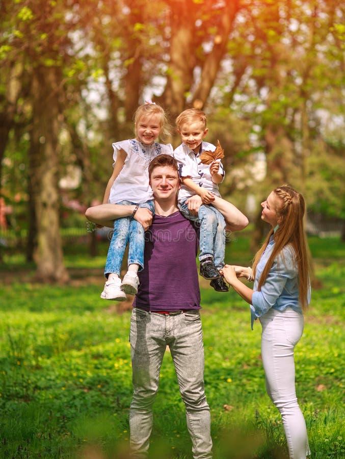 Retrato de la familia que se divierte en parque de florecimiento de la ciudad en el día soleado brillante que pasa feliz su tiemp foto de archivo