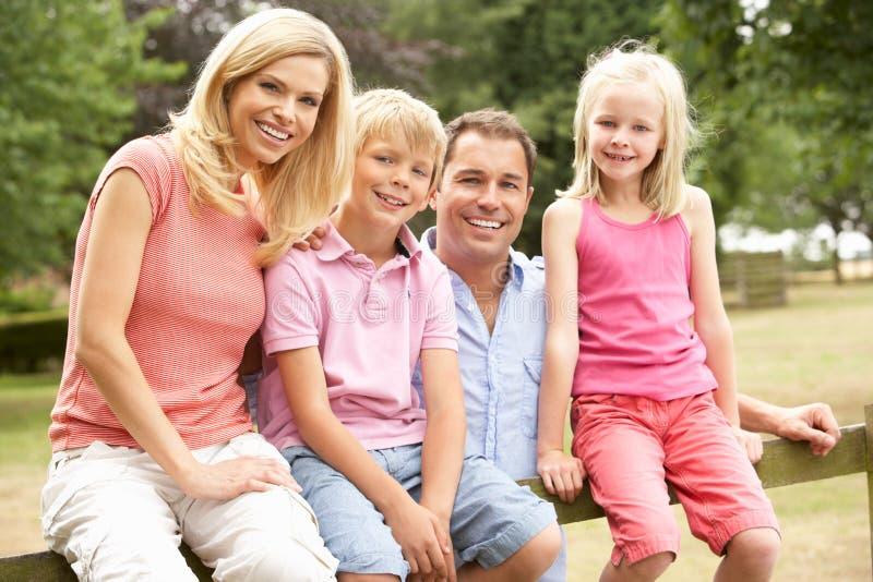 Retrato de la familia que se sienta en la cerca en campo foto de archivo libre de regalías