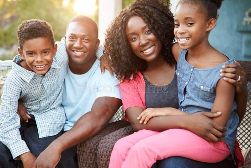 Retrato de la familia que se sienta fuera de casa imagenes de archivo