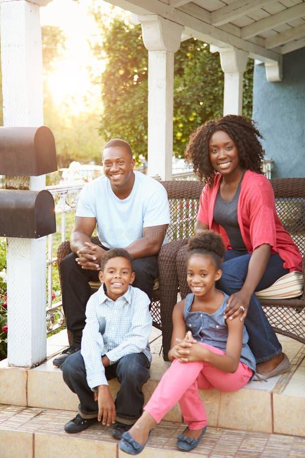 Retrato de la familia que se sienta fuera de casa imagen de archivo