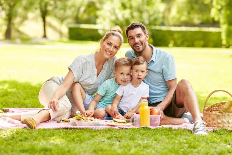 Retrato de la familia que tiene comida campestre en el parque del verano imágenes de archivo libres de regalías