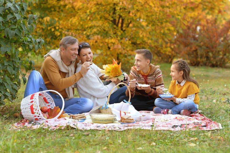 Retrato de la familia que tiene una comida campestre en el parque en oto?o foto de archivo