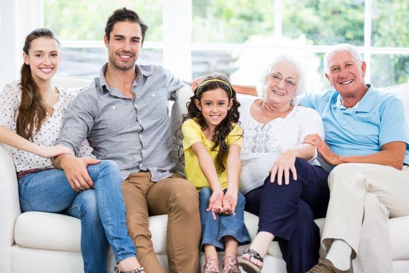 Retrato de la familia sonriente con los abuelos en el sofá fotos de archivo