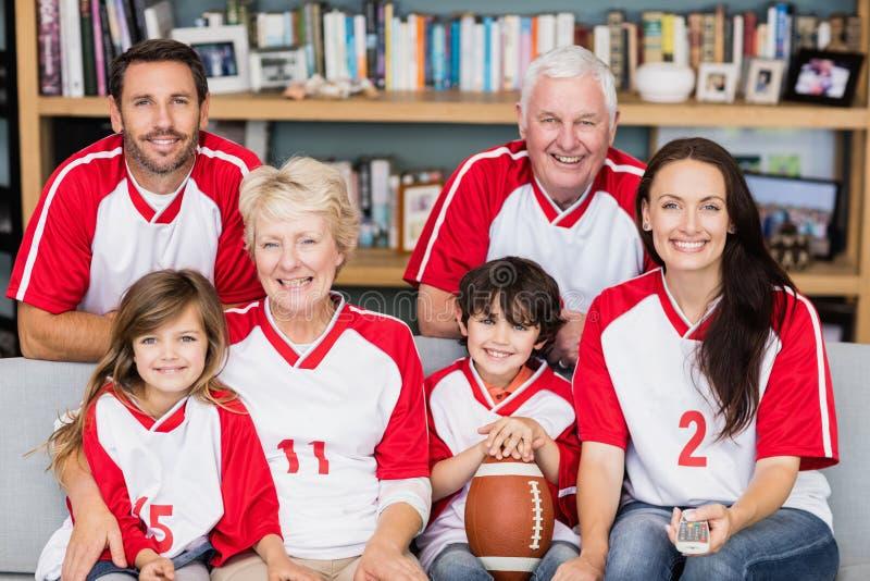 Retrato de la familia sonriente con los abuelos que miran el partido del fútbol americano imagenes de archivo