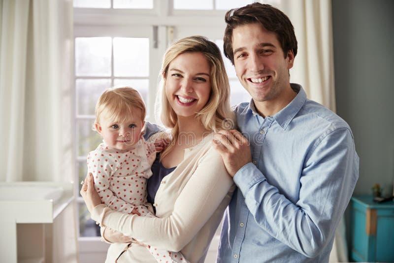 Retrato de la familia sonriente que detiene a la hija del bebé en cuarto de niños fotografía de archivo libre de regalías