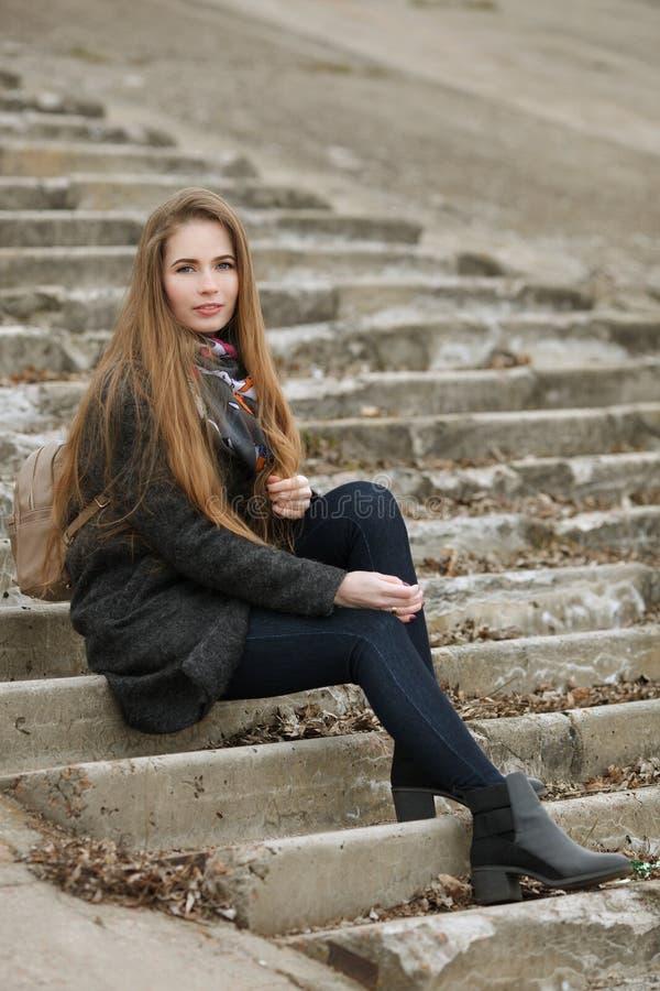 Retrato de la forma de vida de la mujer adulta joven y bonita con el pelo largo magnífico que plantea sentarse en la escalera con foto de archivo