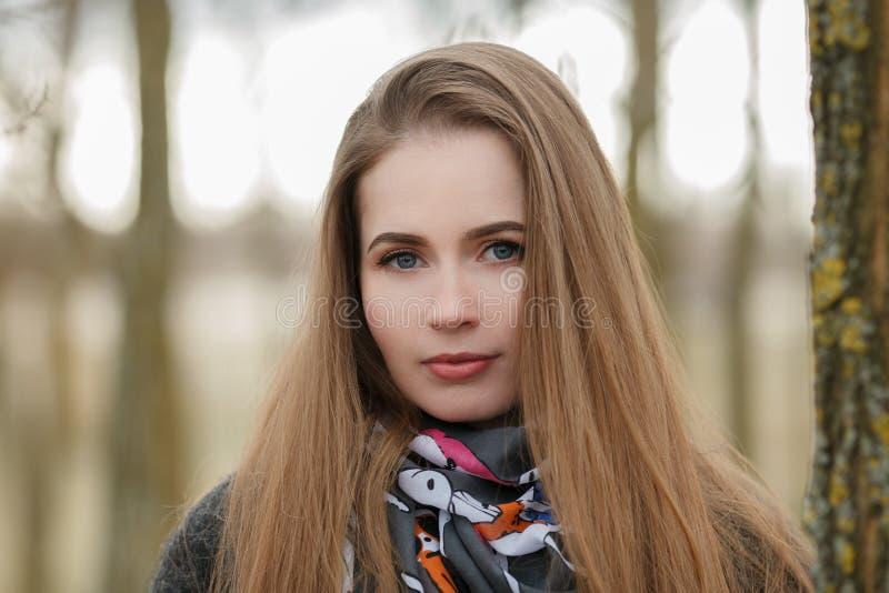 Retrato de la forma de vida de la mujer adulta joven y bonita con el pelo largo magnífico que presenta en parque de la ciudad con imagenes de archivo