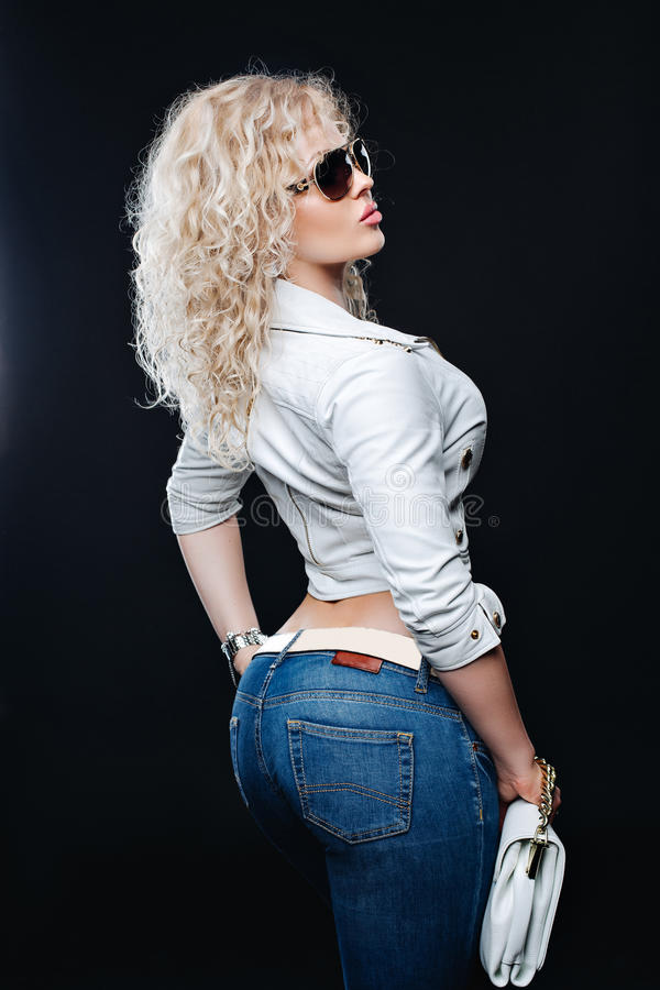 Retrato de la forma de vida de la mujer joven de moda con el pelo rubio rizado, gafas de sol, chaqueta de cuero blanca, tejanos fotos de archivo
