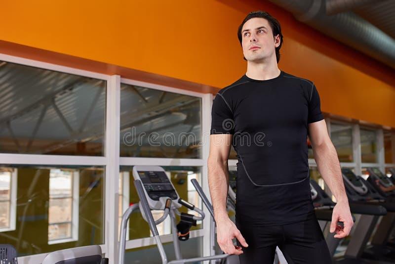 Retrato de la forma de vida del hombre muscular hermoso en la camiseta negra que se opone en el gimnasio del deporte al simulador imagen de archivo