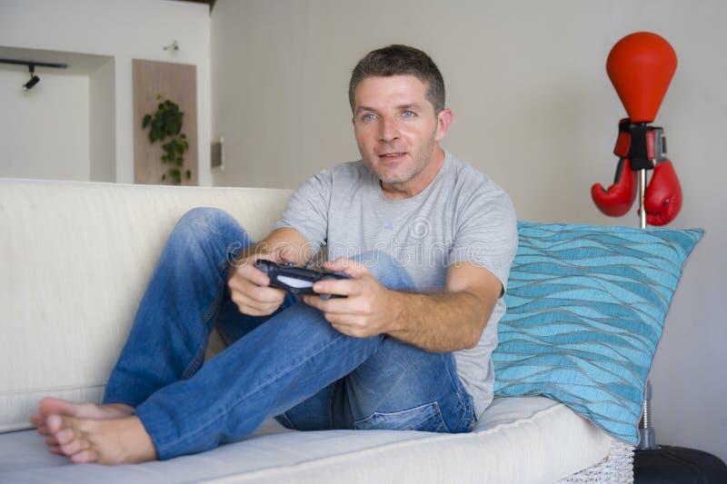Retrato de la forma de vida del individuo atractivo y feliz joven que goza jugando el sofá del sofá de la sala de estar del video foto de archivo