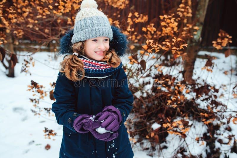 retrato de la forma de vida del invierno de la muchacha feliz del niño que juega bolas de nieve en el paseo foto de archivo