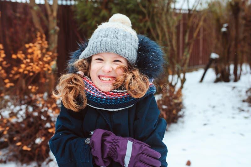 retrato de la forma de vida del invierno de la muchacha feliz del niño que juega bolas de nieve en el paseo imágenes de archivo libres de regalías