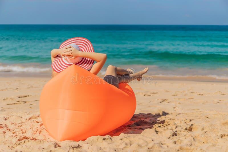 Retrato de la forma de vida del verano de la muchacha bonita que se sienta en el sofá inflable anaranjado en la playa de la isla  fotos de archivo