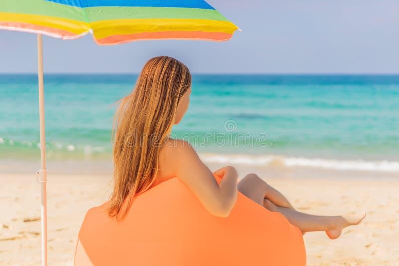 Retrato de la forma de vida del verano de la muchacha bonita que se sienta en el sofá inflable anaranjado en la playa de la isla  imágenes de archivo libres de regalías