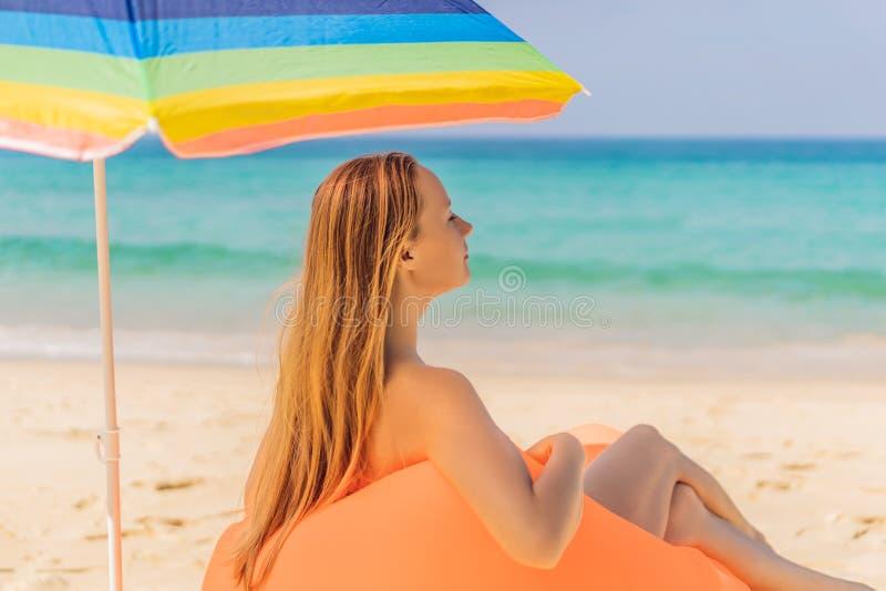 Retrato de la forma de vida del verano de la muchacha bonita que se sienta en el sofá inflable anaranjado en la playa de la isla  foto de archivo