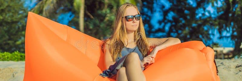 Retrato de la forma de vida del verano de la muchacha bonita que se sienta en el sofá inflable anaranjado en la playa de la isla  imagen de archivo
