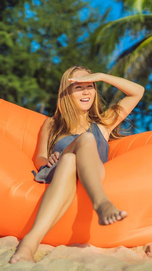 Retrato de la forma de vida del verano de la muchacha bonita que se sienta en el sofá inflable anaranjado en la playa de la isla  imagen de archivo libre de regalías