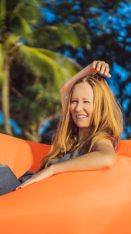 Retrato de la forma de vida del verano de la muchacha bonita que se sienta en el sofá inflable anaranjado en la playa de la isla  fotografía de archivo