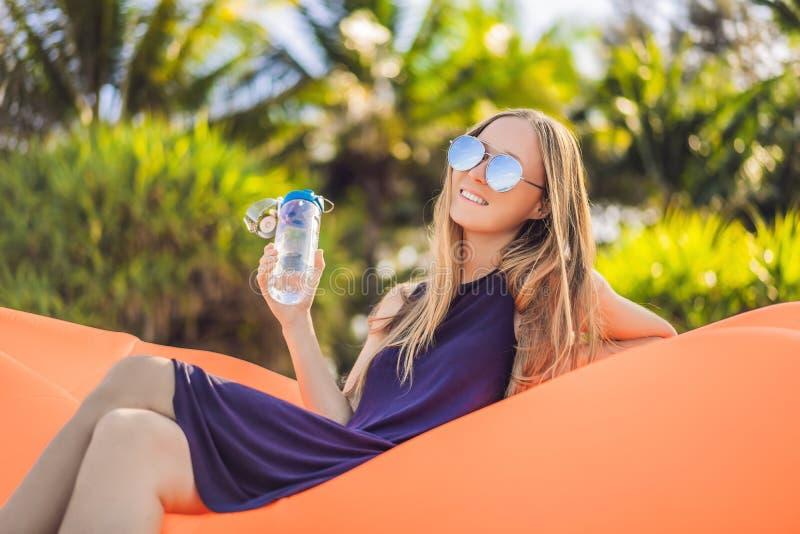 Retrato de la forma de vida del verano de la muchacha bonita que se sienta en el sof? inflable anaranjado y el agua potable en la foto de archivo