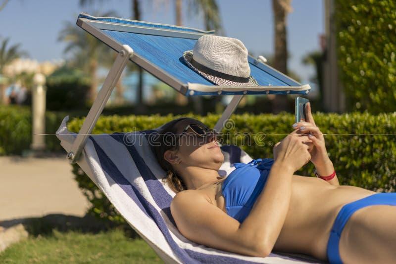 Retrato de la forma de vida del verano de la mujer imponente joven que miente en sunbed en la playa del smartphone tropical de la imagenes de archivo