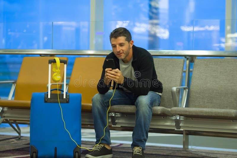 Retrato de la forma de vida en aeropuerto del hombre turístico atractivo y feliz joven con la maleta usando el teléfono móvil en  fotografía de archivo libre de regalías