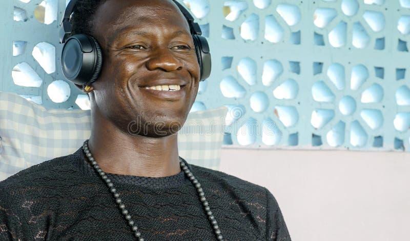 Retrato de la forma de vida de escuchar alegre sonriente joven del hombre afroamericano negro fresco atractivo y feliz la música  imagenes de archivo