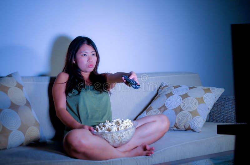 Retrato de la forma de vida de la mujer coreana asiática dulce y feliz joven que goza mirando la televisión usando el la telediri imágenes de archivo libres de regalías