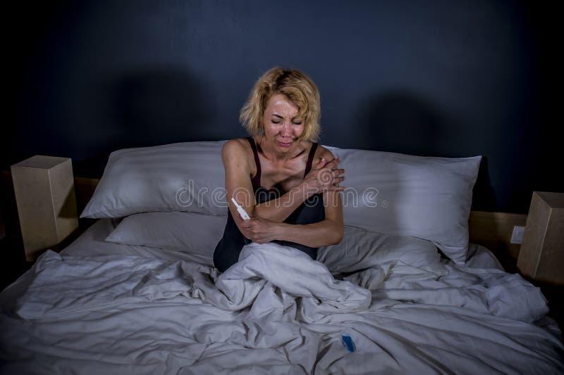 Retrato de la forma de vida de la mujer embarazada desesperada joven que usa la prueba de embarazo triste y deprimida para la esp imagen de archivo libre de regalías