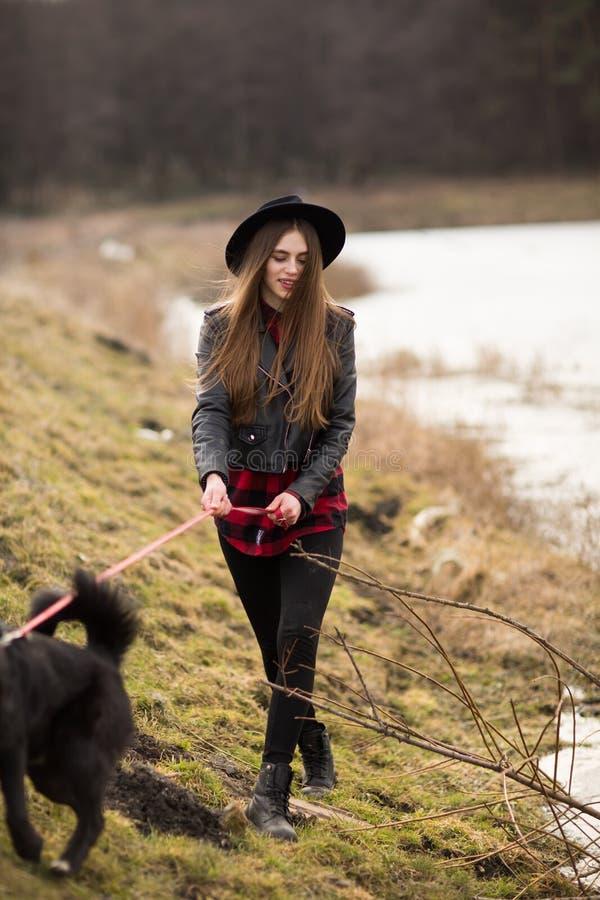 Retrato de la forma de vida de la mujer joven en sombrero negro con su perro, caminando por el lago en un d?a agradable y calient imagen de archivo