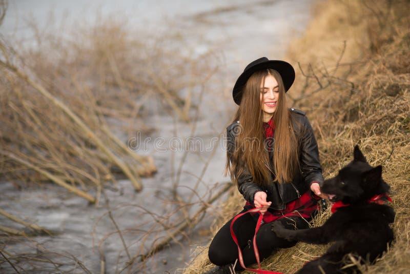 Retrato de la forma de vida de la mujer joven en sombrero negro con su perro, descansando por el lago en un día agradable y calie imagenes de archivo