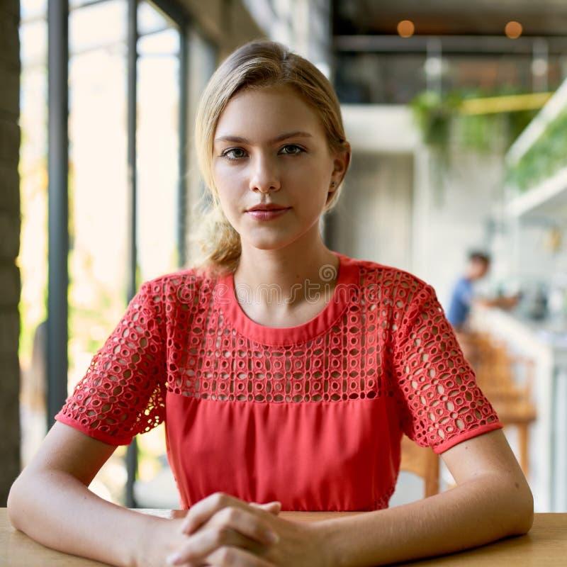 Retrato de la forma de vida de la mujer milenaria de moda joven confiada con el pelo rubio que se sienta en la tabla de madera en foto de archivo