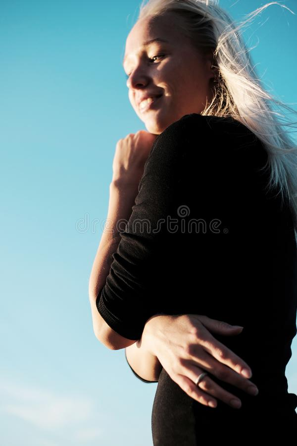 Retrato de la forma de vida de la mujer rubia joven con sonrisa en vestido negro imagen de archivo