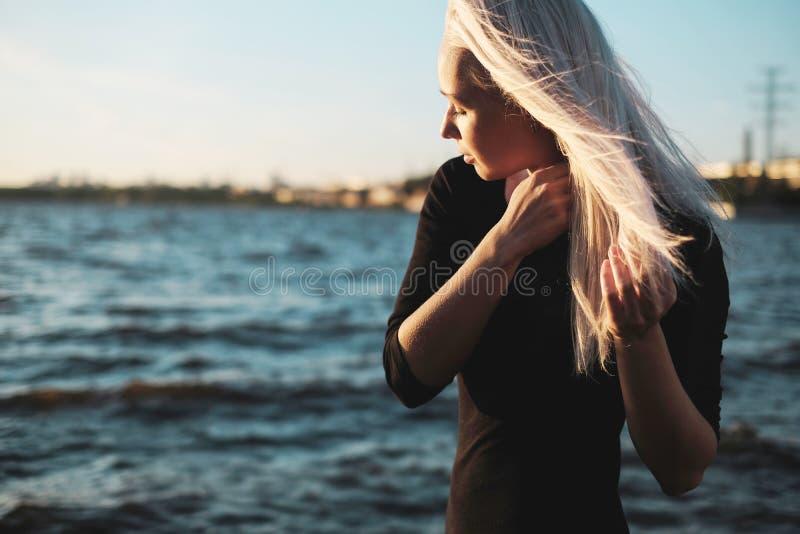 Retrato de la forma de vida de la mujer rubia joven del smilyng en día ventoso en la puesta del sol imágenes de archivo libres de regalías