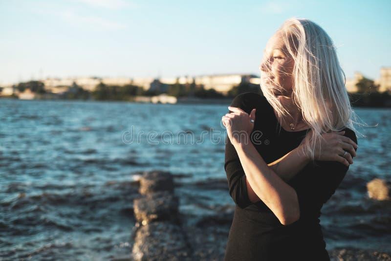 Retrato de la forma de vida de la mujer rubia joven del smilyng en día ventoso en la puesta del sol imagen de archivo libre de regalías