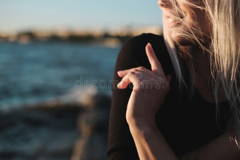 Retrato de la forma de vida de la mujer rubia joven del smilyng en la puesta del sol fotos de archivo