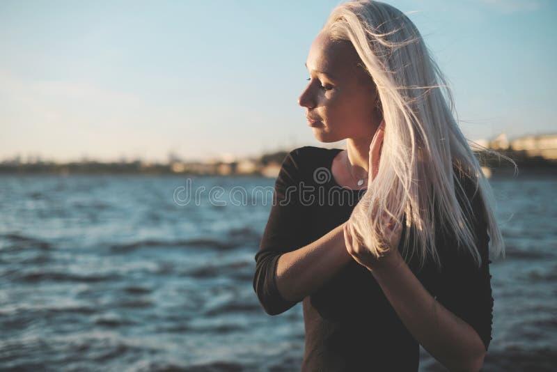Retrato de la forma de vida de la mujer rubia joven en día ventoso en la puesta del sol imagen de archivo