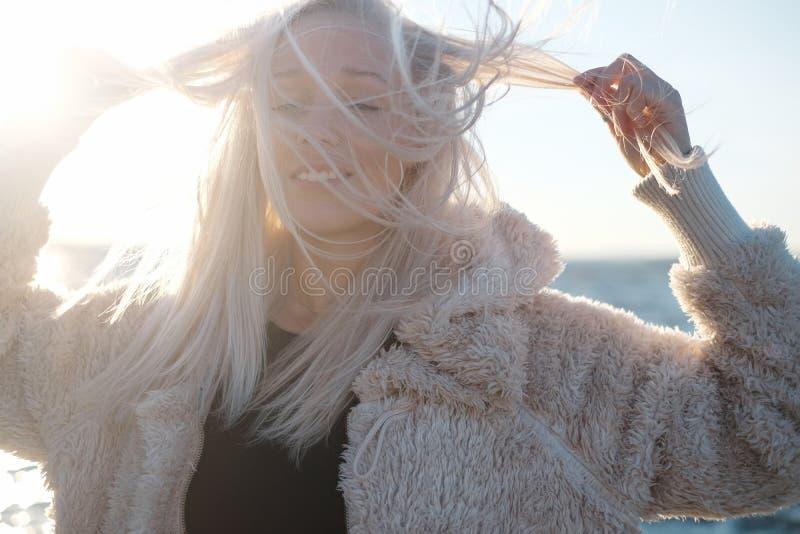 Retrato de la forma de vida de la mujer rubia joven en la puesta del sol con el mar fotos de archivo libres de regalías