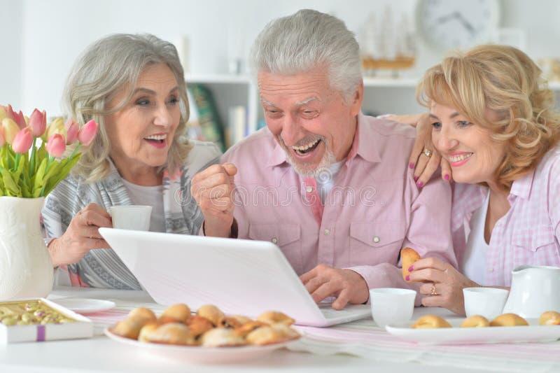 Retrato de la gente mayor feliz con t? de consumici?n del ordenador port?til foto de archivo libre de regalías