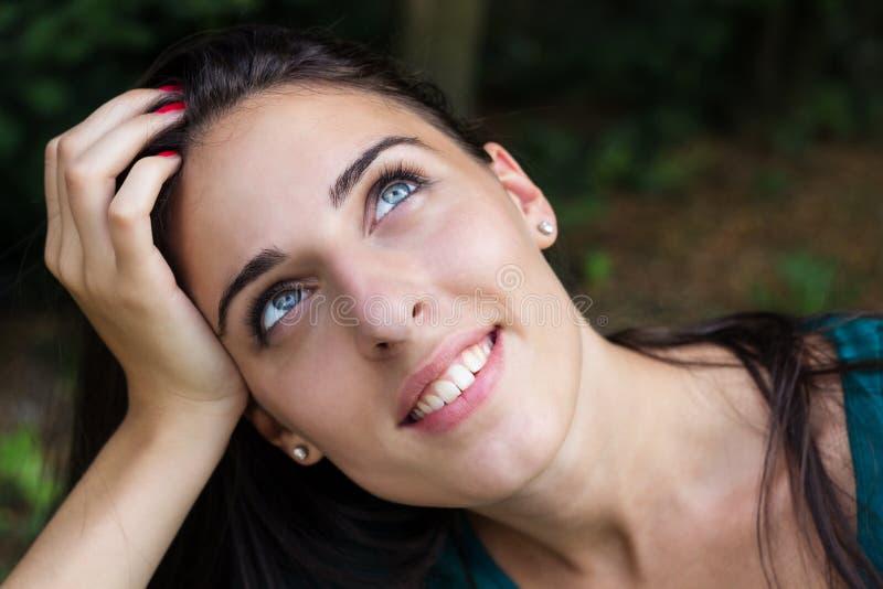 Retrato de la hembra hermosa sonriente que mira para arriba imagen de archivo