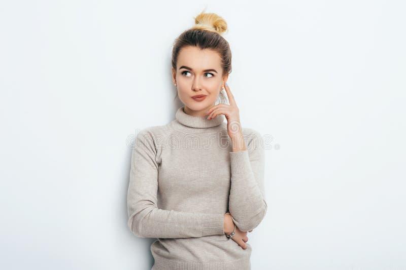 Retrato de la hembra joven pensativa atractiva que lleva su pelo rubio en el nudo que sostiene el índice para arriba que mira lej foto de archivo