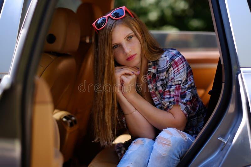 Retrato de la hembra pecosa en un coche imagenes de archivo