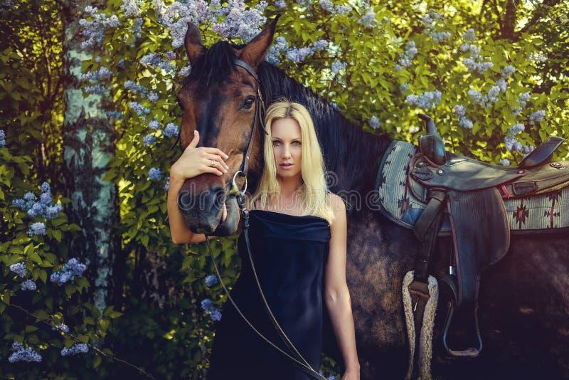 Retrato de la hembra rubia con el caballo imagenes de archivo