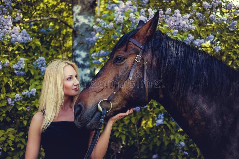 Retrato de la hembra rubia con el caballo fotografía de archivo