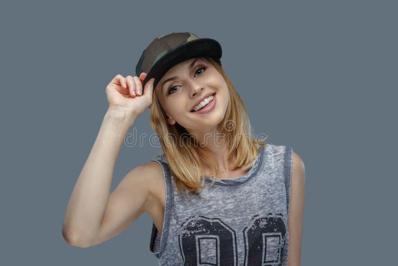 Retrato de la hembra rubia positiva en gorra de béisbol imagen de archivo libre de regalías