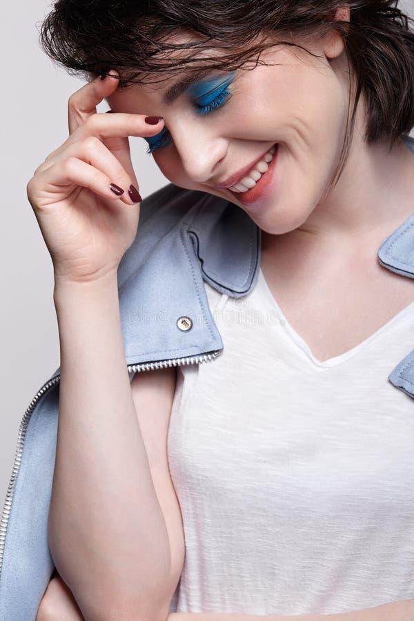 Retrato de la hembra sonriente en chaqueta azul Mujer con maquillaje inusual de la belleza y pelo mojado, y maquillaje azul de la fotos de archivo